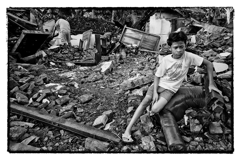 A Indonesian earthquake survivor sits outside his damaged home