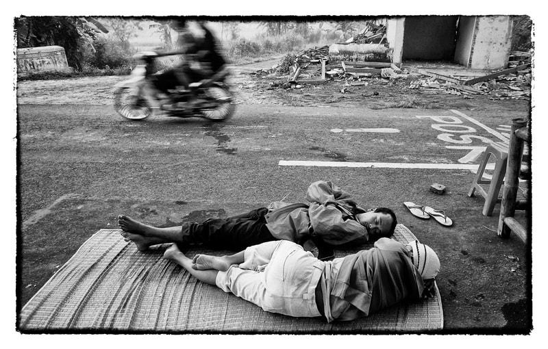 Men sleep on the street following an earthquake in Indonesia