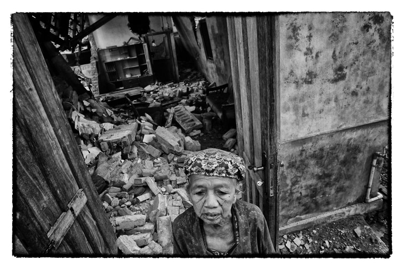 Indonesian woman outside earthquake damaged home